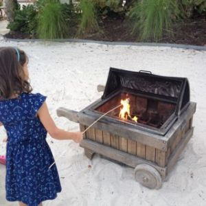 My daughter roasting marshmallows on a fake beach.